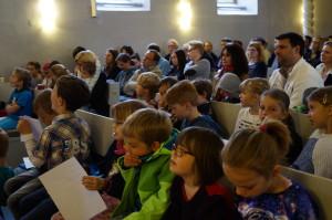 Kinder und Erwachsene sitzen in der Kirche
